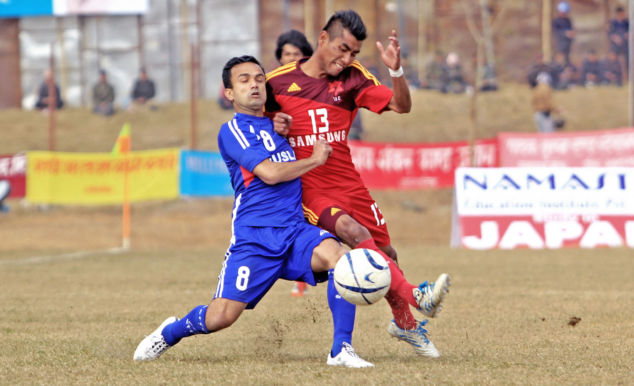 A Three Star Club player (Blue) vies for the ball with a Tribhuvan Army Club player during the 14th Aaha-Rara Gold Cup in Pokhara, on Monday, January 25, 2016. Photo: THT
