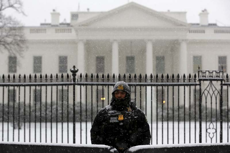 A member of the Uniformed Division of the Secret Service stands at his post in the snow at the White House in Washington on January 22, 2016. Photo: Reuters