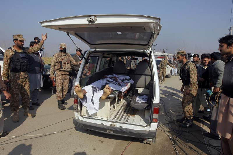 Pakistani troops clear way for an ambulance transporting a lifeless body of a victim from Bacha Khan University in Charsadda town, some 35 kilometers (21 miles) outside the city of Peshawar, Pakistan, on Wednesday, January 20, 2016. Photo: AP