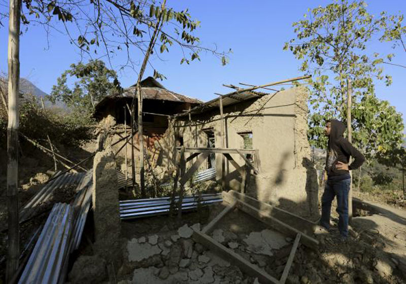 A man stands next to a damaged house after an earthquake at P.Molding village on the outskirts of Imphal, January 4, 2016. Photo: Reuters
