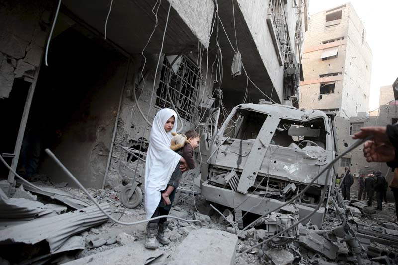 A girl carrying a baby inspects damage at a site hit by what activists said were airstrikes carried out by the Russian air force in the town of Douma, eastern Ghouta in Damascus, Syria on January 10, 2016. Photo: Reuters