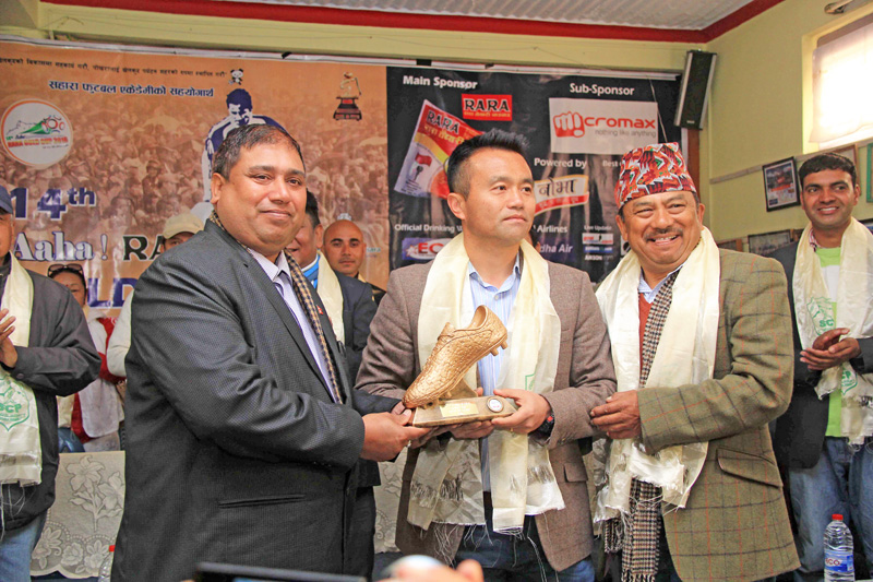 Sahara UK treasurer Narayan Gurung handing over a trophy to Sahara Club President Bir Bhadra Acharya (left) at a press meet in Pokhara on nSunday. The trophy will be awarded to the best player of the tournament. Photo: THT