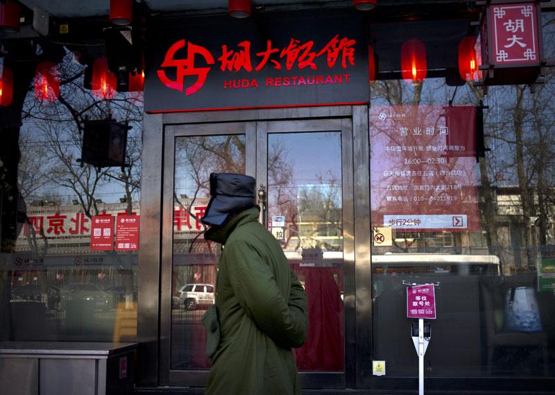 A man walks past a branch of the Hu Da hot pot restaurant chain in Beijing, on Friday, January 22, 2016. Photo: AP