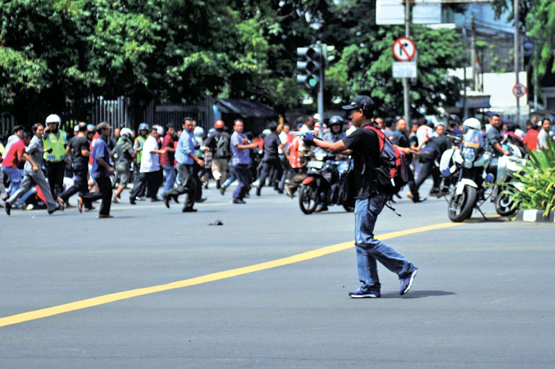 A man is seen holding a gun towards the crowd in central Jakarta, in this picture provided to Reuters by Xinhua News Agency on Thursday.  Photo: Reuters