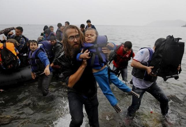File photograph shows a volunteer carrying a Syrian refugee child off an overcrowded dinghy at a beach after the migrants crossed part of the Aegean Sea from Turkey to the Greek island of Lesbos September 23, 2015.  REUTERS/Yannis Behrakis/files