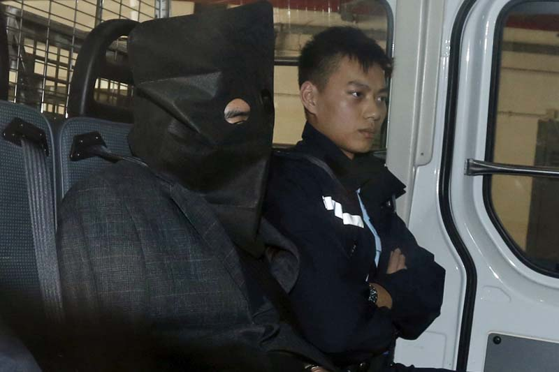 Deyun Shi (left), sitting beside a police officer inside a police van, arrives at a magistrate court in Hong Kong, China on January 25, 2016. Photo: Reuters