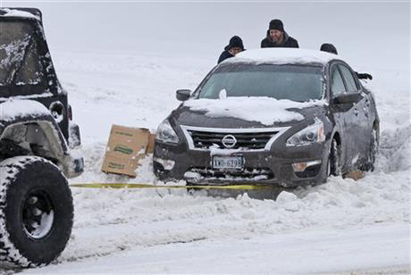 Passers-by help push a stuck car out of the snow as another motorist tows it out in Richmond, Va., Saturday, Jan. 23, 2016. Photo: AP