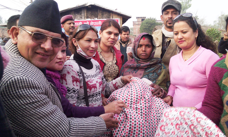 Chief District Officer of Rautahat, Narahari Baral (left), distributing quilts and mattresses to Dalit families, in Gaur, Rautahat, on Thursday. Photo: THT