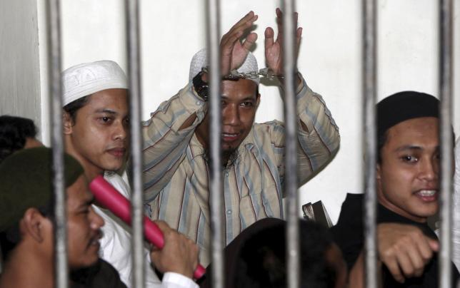 Radical Muslim cleric Aman Abdurrahman (C), also known as Oman Rochman, raises his hands in a holding cell as he waits with other militants for their trial in Jakarta, in this August 26, 2010 file photo.  REUTERS/Dadang Tri/Files