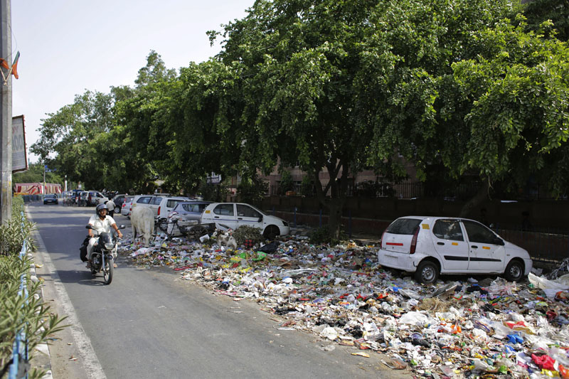 FILE -  An Indian motorist rides past an overflowing roadside garbage-dumping site in New Delhi, India on June 12, 2015. Photo: AP