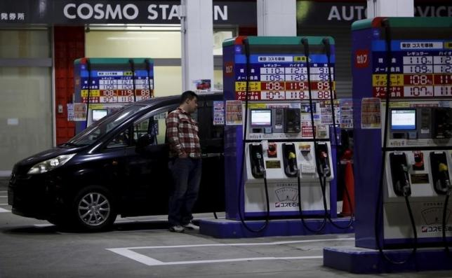 A man stands to wait for refueling for his car at Cosmo Energy Holdings' Cosmo Oil service station in Tokyo, Japan, December 16, 2015. Picture taken December 16, 2015. Photo: Reuters