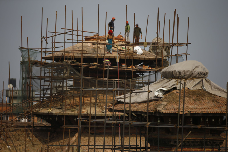 Labourers perform construction works on the top of Taleju Temple, which was damaged by the last year earthquakes, in Patan, Lalitpur on Friday, January 29, 2016. Photo: Skanda Gautam/ THT