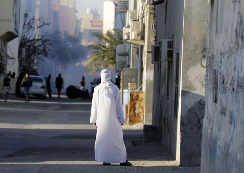 A Bahraini man watches anti-government protesters clashing with riot police firing tear gas, in Sitra, Bahrain, on Sunday, February 14, 2016. Photo: AP
