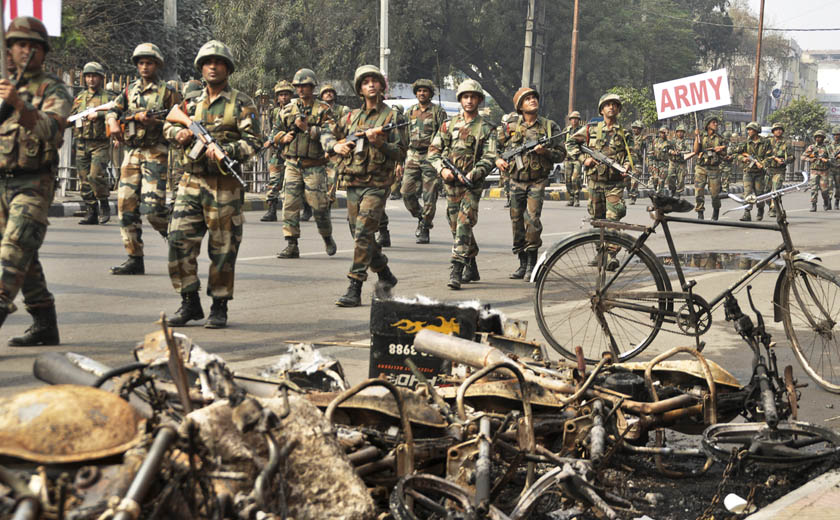 Indian army soldiers conduct a flag march at Rohtak, that was Friday rocked by violence in Haryana state, India, Saturday, Feb.20, 2016. Hundreds of army and paramilitary soldiers on Saturday tried to quell protests by angry mobs demanding government benefits in the northern Indian state, with at least four people killed in clashes between security forces and protesters, officials said. Photo: AP