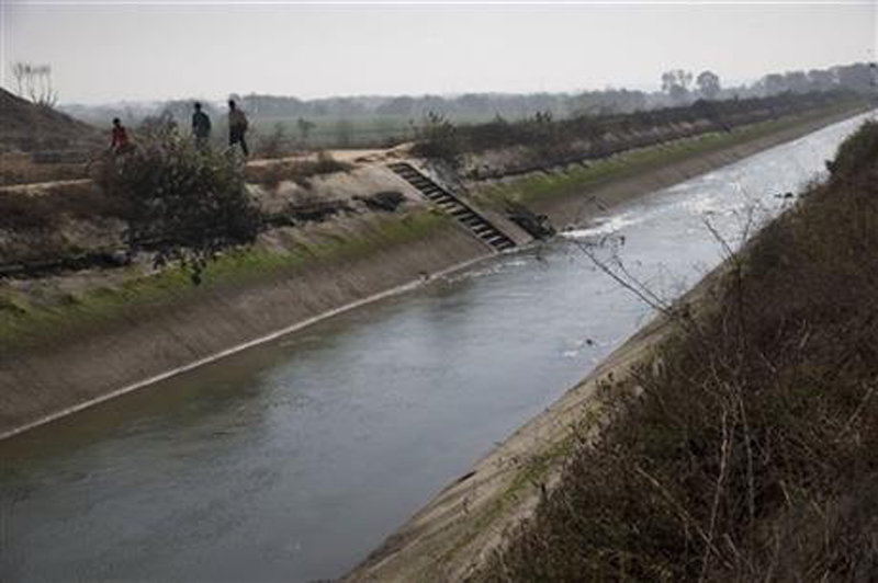 Villagers walk next the Munak canal, near the village of Bindroli, India, Monday, Feb. 22, 2016. Fears of a water crisis in the Indian capital eased Monday with security forces securing a canal in Haryana, which provides 60 percent of its water needs. AP