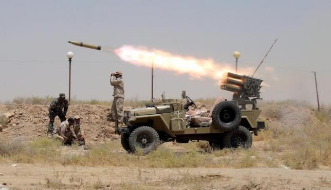 Members of Iraq's Shi'ite paramilitaries launch a rocket towards Islamic State militants in the outskirts of the city of Falluja, in the province of Anbar, Iraq July 12, 2015.  REUTERS/Stringer