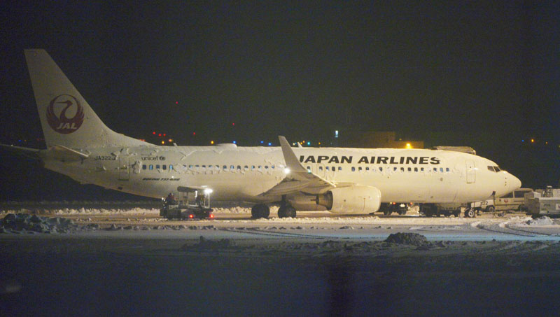 Japan Airlines' Boeing 737 passenger plane sits on the snow-covered tarmac after passengers and crew slid down emergency chutes at New Chitose Airport in Sapporo, northern Japan, on  Tuesday, February 23, 2016. Photo: Daisuke Suzuki/Kyodo News via AP