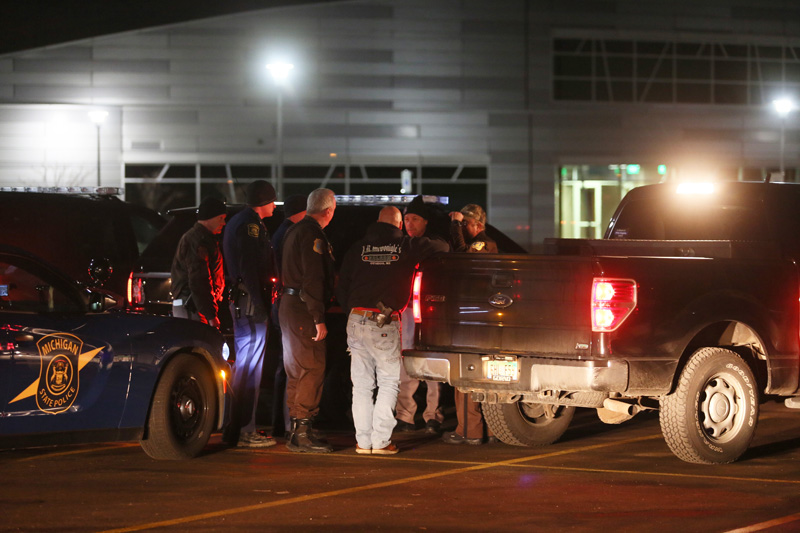 Police meet early Sunday at Kalamazoo Valley Community College after searching for a gunman involved in multiple shootings Saturday, February 20, 2016 in Kalamazoo, Michigan. Photo: AP