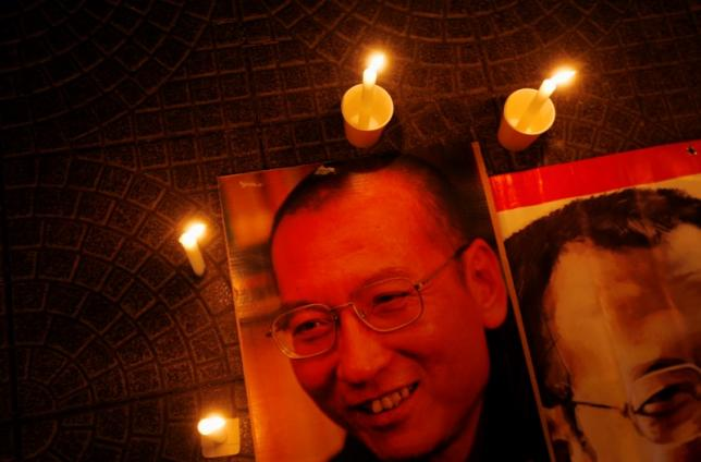 Candles are placed around portraits of jailed Chinese pro-democracy activist Liu Xiaobo during a candlelight vigil demanding his release, outside the Legislative Council in Hong Kong November 2, 2010. It is unclear who will accept the Nobel Peace Prize awarded to jailed Chinese dissident Liu Xiaobo and the Norwegian Nobel Committee may keep custody of it for the time being, its secretary said last week. REUTERS/Bobby Yip   (CHINA - Tags: POLITICS CIVIL UNREST) - RTXU48Z