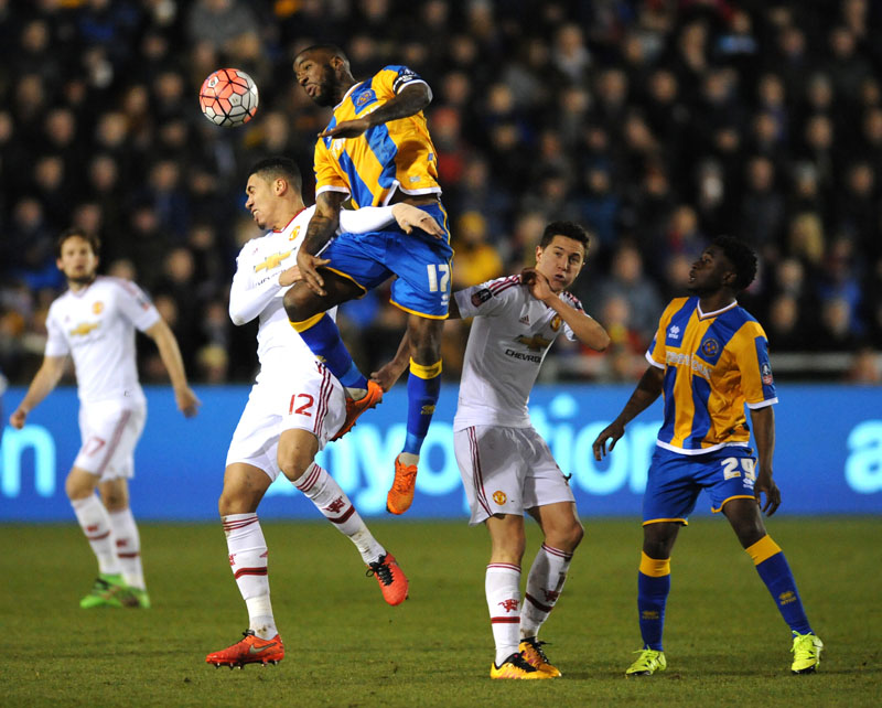 Shrewsburyu0092s Abu Ogogo (centre right) battles for the ball with Manchester Unitedu0092s Chris Smalling during the English FA Cup fifth round soccer match between Shrewsbury Town and Manchester United at Greenhous Meadow stadium in Shrewsbury, England, on Monday, February 22, 2016. Photo: AP