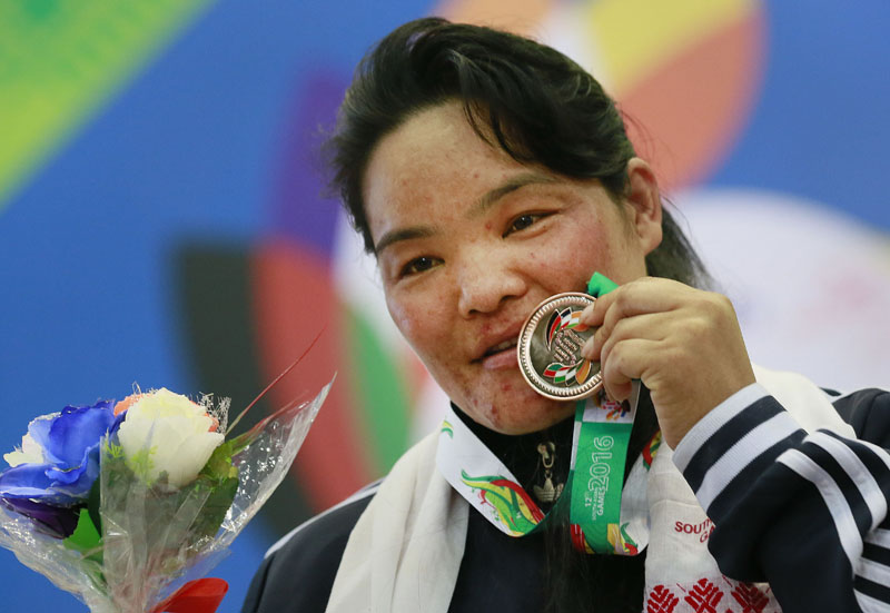 Nepal's Tara Devi Pun displays her silver medal in the 75 kg women weightlifting event during the 12th South Asian Games in Guwahati, India, on Tuesday, February 9, 2016. Photo: AP