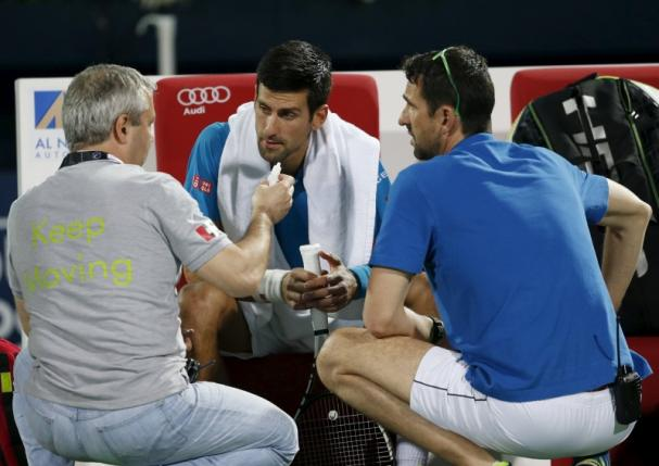 Novak Djokovic of Serbia receives treatment before withdrawing from his match against Feliciano Lopez of Spain at the ATP Dubai Duty Free Tennis Championships February 25, 2016. REUTERS/Ahmed Jadallah