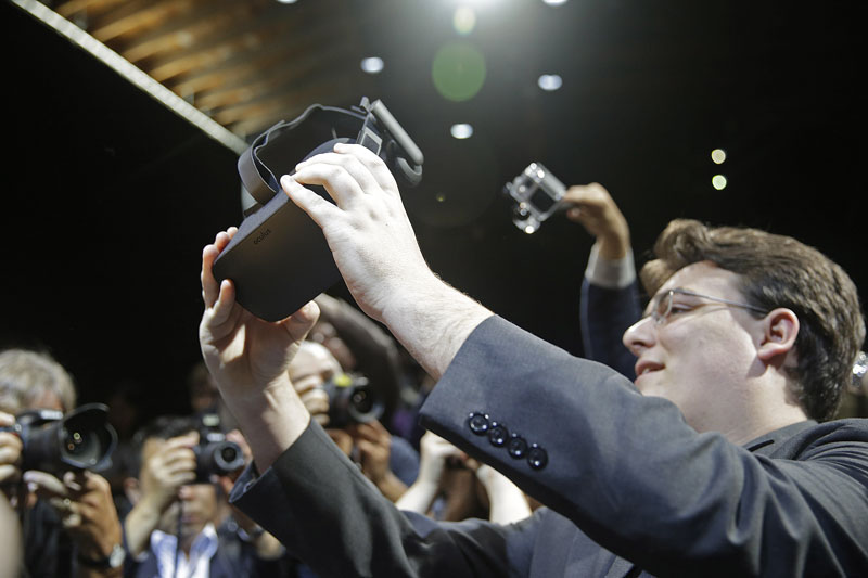 Oculus founder Palmer Luckey holds up the new Oculus Rift virtual reality headset for photographers following a news conference, in San Francisco, on June 11, 2015. Photo: AP/ File