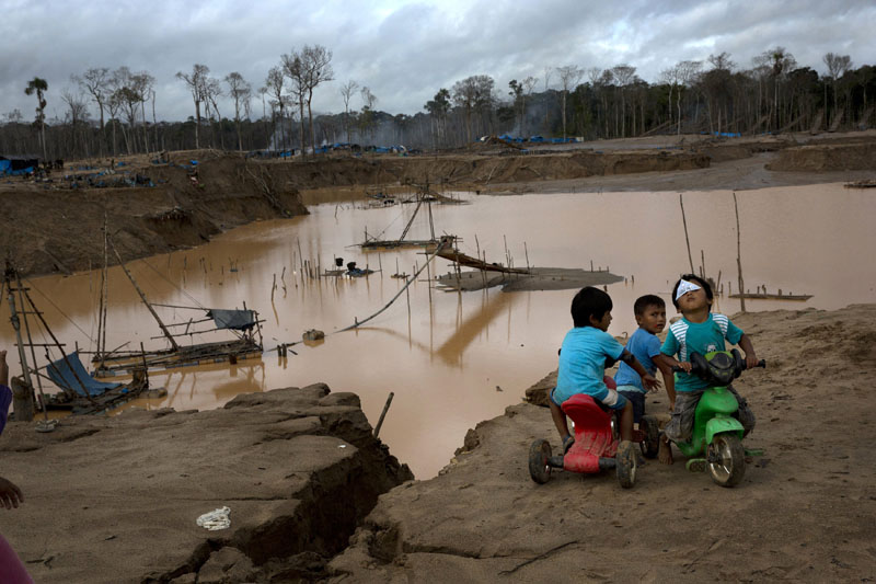 Children play next to a crater, created by gold mining, during a government raid to dismantle the illegal wildcat operation in La Pampa, in Peru's Madre de Dios region, on Tuesday, February 23, 2016. Photo: AP