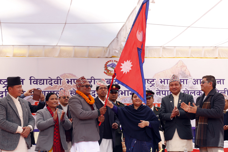 President Bidya Devi Bhandari hands over the national flag to Minister for Youth and Sports Satya Narayan Mandal at a function organised to see off the Nepali team which is leaving for India for the 12th South Asian Games, in Kathmandu, on Monday, February 1, 2016. Photo: RSS