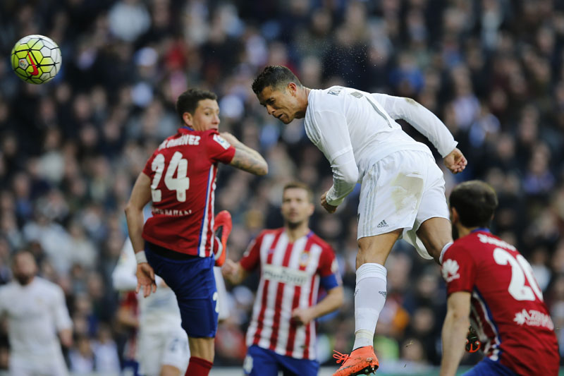 Real Madrid's Cristiano Ronaldo jumps to head the ball towards the goal during a Spanish La Liga soccer match between Real Madrid and Atletico Madrid at the Santiago Bernabeu stadium in Madrid, Spain, on Saturday February 27, 2016. Photo: AP