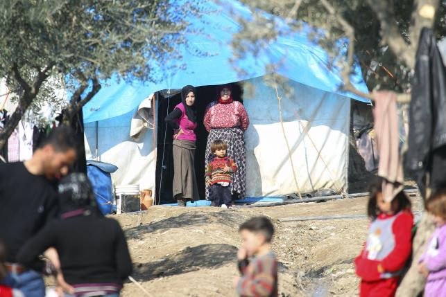 People stand outside tents housing internally displaced people in Salqin town, in Idlib province, Syria February 9, 2016. REUTERS/Ammar Abdullah