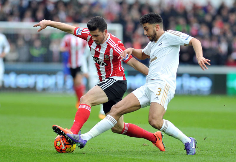 Swansea City's Neil Taylor (right) and Southampton's Shane Long battle for the ball during the English Premier League soccer match at the Liberty Stadium, Swansea, Wales, on Saturday, February 13, 2016. Photo: Simon Galloway/PA via AP
