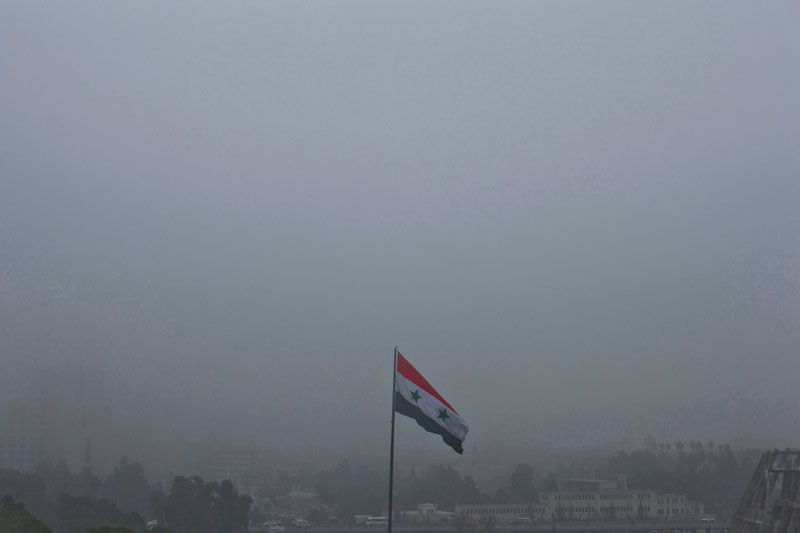A Syrian national flag waves as heavy fog envelops the capital city of Damascus, Syria, on Wednesday, February 24, 2016. Photo: AP