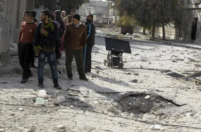 Men stand near a hole in the ground as they inspect the damage after airstrikes by pro-Syrian government forces in the rebel held al-Sakhour neighbourhood of Aleppo, Syria February 5, 2016.  REUTERS/Abdalrhman Ismail