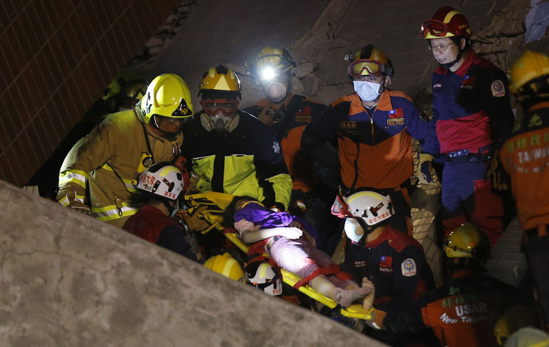 A female is rescued from a collapsed building complex after  an early morning earthquake in Tainan, Taiwan, on Saturday, February 6, 2016. Photo: AP