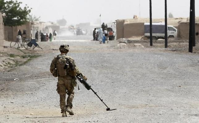 A U.S. Army sapper uses a mine detector to check the road in advance of a dismounted patrol near Combat Outpost Terra Nova in the Arghandab Valley north of Kandahar April 8, 2011.  REUTERS/Bob Strong/Files