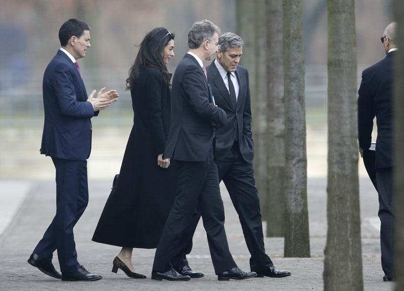 US actor George Clooney (right) and his wife Amal Clooney (second left) are accompanied by Merkel's foreign policy advisor Christoph Heusgen (center) as they leave chancellery after private meeting with German chancellor Angela Merkel in Berlin, Germany, on Friday, February 12, 2016. Photo: AP