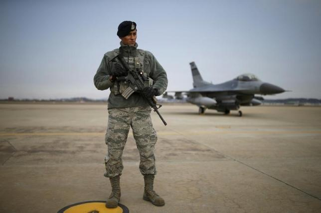 A U.S. soldier stands guard in front of their Air F-16 fighter jet at Osan Air Base in Pyeongtaek, South Korea, January 10, 2016. REUTERS/Kim Hong-Ji