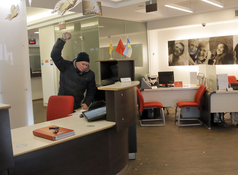 An ultra-right activist throws a brick, at an Alfa bank office in centre of Kiev, Ukraine, on Saturday, February 20, 2016.  Photo: AP