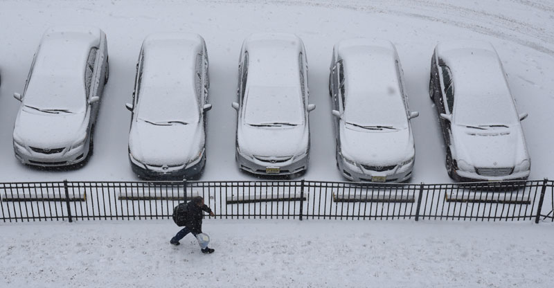 A person walks past parked snow-covered cars Monday, February 15, 2016, in Philadelphia. Photo: Clem Murray/The Philadelphia Inquirer via AP