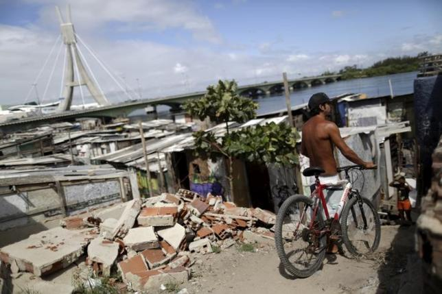 A man stands with a bicycle near his house in the shanty town of Beco do Sururu, Recife, Brazil, January 29, 2016. REUTERS/Ueslei Marcelino
