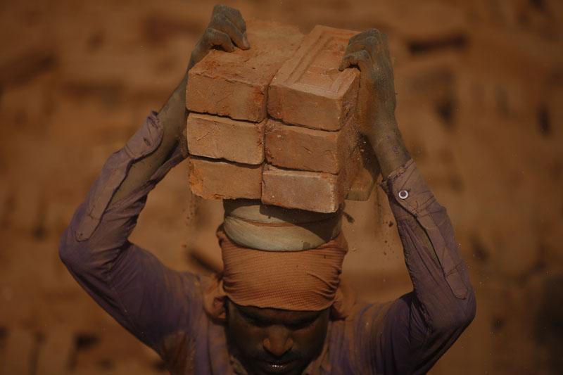 A migrant worker stacks bricks onto his head at a brick kiln in Sipadol, Bhaktapur on Wednesday, February 3, 2016. Photo: Skanda Gautam
