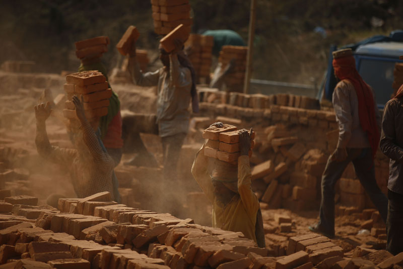 Migrant workers stack bricks onto their heads at a brick kiln in Sipadol, Bhaktapur on Wednesday, February 3, 2016. Photo: Skanda Gautam