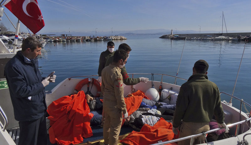 Members of Turkish forces look at the bodies of some of the migrants that were drowned as they were trying to reach Greece, at a port in the coastal town of Dikili, near Izmir, Turkey, on Monday, February 8, 2016. Photo: AP