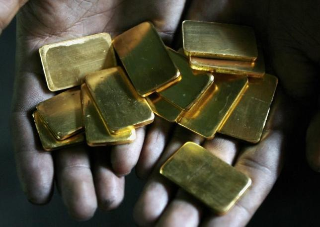A worker shows gold biscuits at a precious metals refinery in Mumbai March 3, 2008. REUTERS/Arko Datta/Files