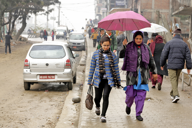 Pedestrians walking with umbrellas to shield themselves from the rain Kathmandu Valley witnessed with the change in weather, on Monday, February 8, 2016. Photo: RSS