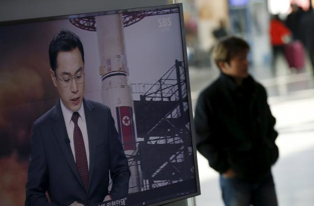 A passenger walks past a TV screen broadcasting a news report on North Korea's long range rocket launch at a railway station in Seoul, South Korea, February 7, 2016. Photo: Reuters