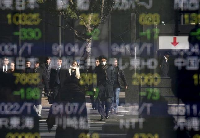People are reflected in a stock quotation board outside a brokerage in Tokyo, Japan January 14, 2016. REUTERS/Toru Hanai