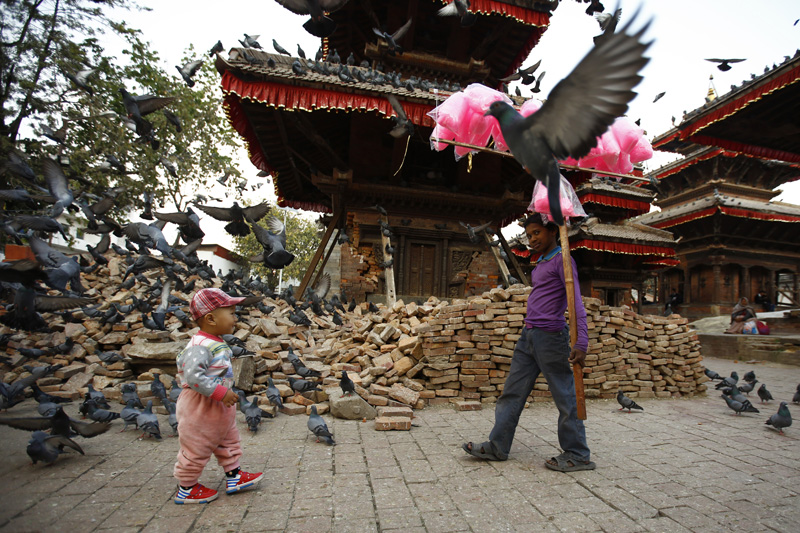 A boy carries cotton candies to sell as a toddler looks on at Hanumandhoka Durbar Square, a UNESCO world heritage site, in Kathmandu on Wednesday, February 24, 2016. Photo: Skanda Gautam