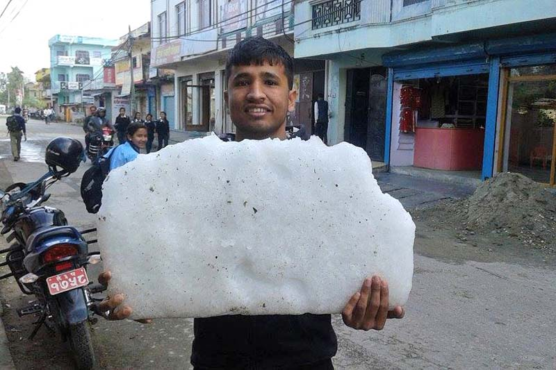 A local man holds a mass of hailstones frozen on a ground in Dhangadhi of Kailali on Monday, March 14, 2016. Photo: Tekendra Deuba/ THT